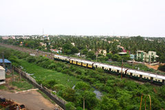 Train Passing through Suburbs of Chennai, India. A metro passenger train passing through Suburbs of Chennai, India Stock Image