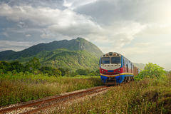 Train passing at sunset against the background of mountains Royalty Free Stock Photo