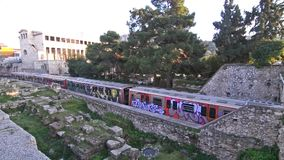 Train passing from Thisio Athens Greece and the ancient Stoa of Attalos behind - european railway stock video