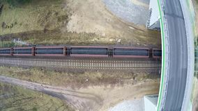 Train passing under the bridge. Aerial view of train carrying coal  in winter landscape stock video footage