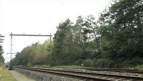 Train passing. Yellow and blue passenger train passing by at high speed stock video footage