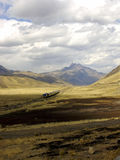 Train in the Peruvian Andes. Train crosses the Altiplano between Puno and Cuzco, with the Andes mountains in the distant background Royalty Free Stock Image