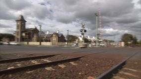 Train rail on a road. A low angle pan to left shot from a train rail. The rail goes to the road stock video footage