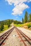 Train Rail way up to mountain in suny day in Austrian alps. Vert Stock Photo