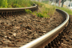 Train rails with rocks. And plants taking a curve Stock Photo