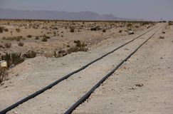 A train rails on the salt flats. A train rails disappears into the distant landscape of the salt flats of Salar de Uyuni in Bolivia royalty free stock photos