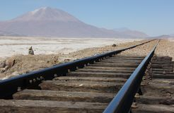 A train rails on the salt flats. A train rails disappears into the distant landscape of the salt flats of Salar de Uyuni in Bolivia royalty free stock photo