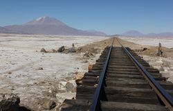 A train rails on the salt flats. A train rails disappears into the distant landscape of the salt flats of Salar de Uyuni in Bolivia royalty free stock images