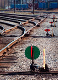 Train rails and switch flags. Overlapping train tracks in a train yard with green and red switch flags stock image