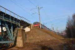 Train on railway bridge. Train geginning to cross railway bridge with the sunny blue sky in the background Stock Image