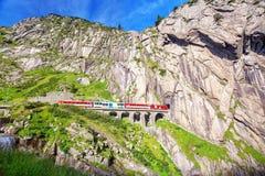 Train on the railway bridge Teufelsbrucke over Reuss river in St. Gotthard mountain range of Swiss Alps near Andermatt Stock Photo