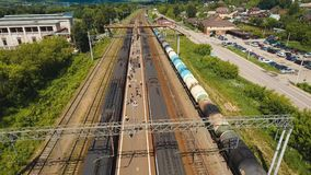Train on the railway. Passenger train arrives at the railway station. Aerial view train, railway, highway. Aerial drone footage, 4k stock video