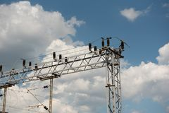Train or railway power line support. Railway power lines with high voltage electricity on metal poles against blue sky. Communication and transmission stock image