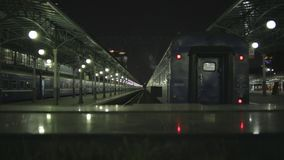 Train on railway station at night. Train on railway station with steam from top, at night in Moscow, Russia. 8 September 2017 stock video footage
