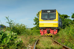 Train on railway track with and green grass and blue sky backgro Stock Photos