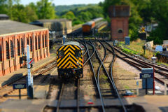 Train on railway track. Tilt shift. Train leaves a station with railway shed on left. Tilt shift effect which renders the image looking like a model railway royalty free stock photos