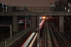 Train Railway Under Gray Overpass during Nightime Royalty Free Stock Image