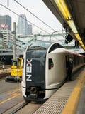 Train rapide de Narita à la station de Shinjuku avec le backg de tour de cocon Photos stock