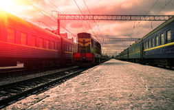 Train in the rays of the red sun Stock Photo