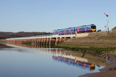 Train on Refurbished Arnside Viaduct at high tide Stock Photo