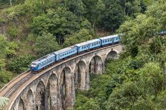 Train on Nine Arches bridge in hill country of Sri Lanka. The train ride through hill country from Kandy to Ella is one of the most beautiful travels by train in Stock Photos