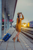 Train ride. Petty girl waiting at the railway station with a suitcase,train station with a train about to leave while the next train waits to come in Stock Photos