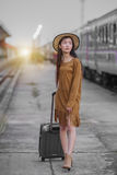 Train ride. Petty girl waiting at the railway station with a suitcase,train station with a train about to leave while the next train waits to come in Royalty Free Stock Images