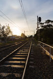 Train ride into the sun. Railway track disappearing into the horizon while sun is setting Stock Photos
