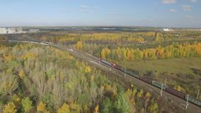 Train rides through an autumn forest on the horizon you can see the city. Train rides on the stretch around the autumn forest. Russia, aerial view stock footage