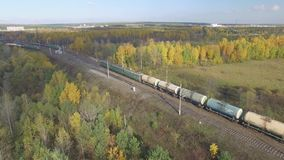 Train rides through an autumn forest on the horizon you can see the city. stock video footage