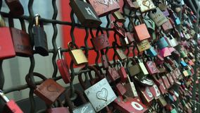 Koln, Germany - October 9, 2017 - Train move behind walls of lovers with locks. The train rides behind the walls of lovers with locks. A lot of locks with words stock video footage
