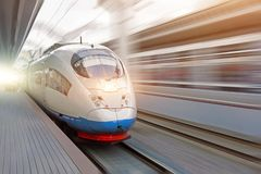 Train rides at high speed at the railway station in the city stock photo