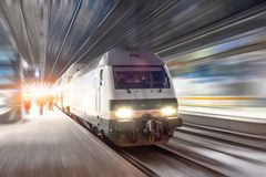 Train rides at high speed at the railway station in the night city royalty free stock photography