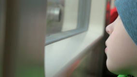 In train rides a little boy in a cap who looks out the window stock video