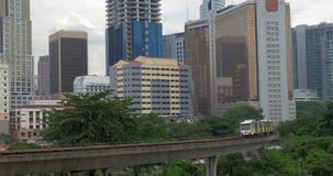 Train riding through Kuala Lumpur, Malaysia. Overground trains moving across Kuala Lumpur on the background of cityscape with high-rise architecture, Malaysia stock footage