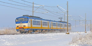 Train riding through a snowy landscape Royalty Free Stock Photo