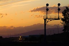 A train rolls through curves at sunset. A short train rolls through curves and past a railroad signal with a colorful sunset behind Stock Photo
