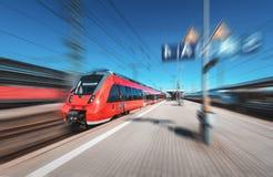 Train rouge à grande vitesse dans le mouvement sur la gare ferroviaire Image stock