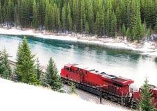Train rouge voyageant le long de la voie ferrée par la forêt W d'hiver image stock
