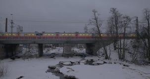Train running across the bridge in winter city. Helsinki, Finland. HELSINKI, FINLAND - JANUARY 07, 2017: Commuter train running over the bridge in evening winter stock video
