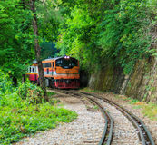 Train running beside the mountain. And pass through the tunnel in Kanchanaburi province of Thailand stock photo
