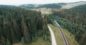Train running over railway in forest. Train running over railway in coniferous forest, aerial view stock video footage