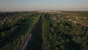 Train running in the village, aerial view. Aerial view of countryside with summer houses and freight train traveling through it, Russia stock footage