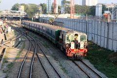 The train runs on the railway tracks and people sit on the train locomotive at Yangon stock photography