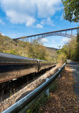 Train runs under the New River Gorge Bridge in West Virginia Stock Photo