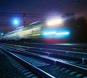 Train rushes on rails. At night Stock Photo