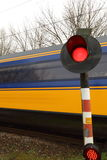 Train rushing past railway crossing. Blue/yellow train rushing past warning light at a railway crossing Royalty Free Stock Images