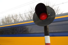 Train rushing past railway crossing. Blue/yellow train rushing past warning light at a railway crossing Stock Image