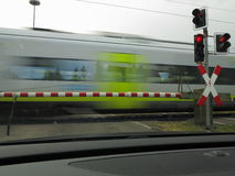 Train rushing by at railroad crossing Royalty Free Stock Image