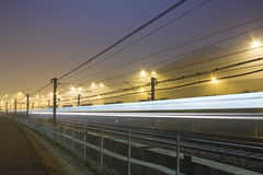 Train's light. Rails by night with reflecting neon light Stock Image